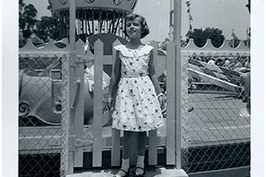 Carol Ann in front of Dumbo Ride. Disneyland July, 1956.