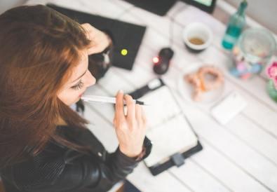 femeie la birou notând pe agendă