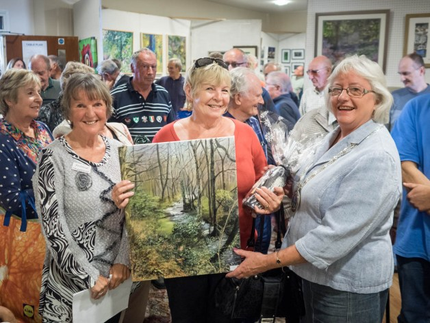 Voted the best piece of art at the show by the visitors ????? with ????? receives her award from Town Mayor Carol McKensie and Sheila Brooster, festival organiser