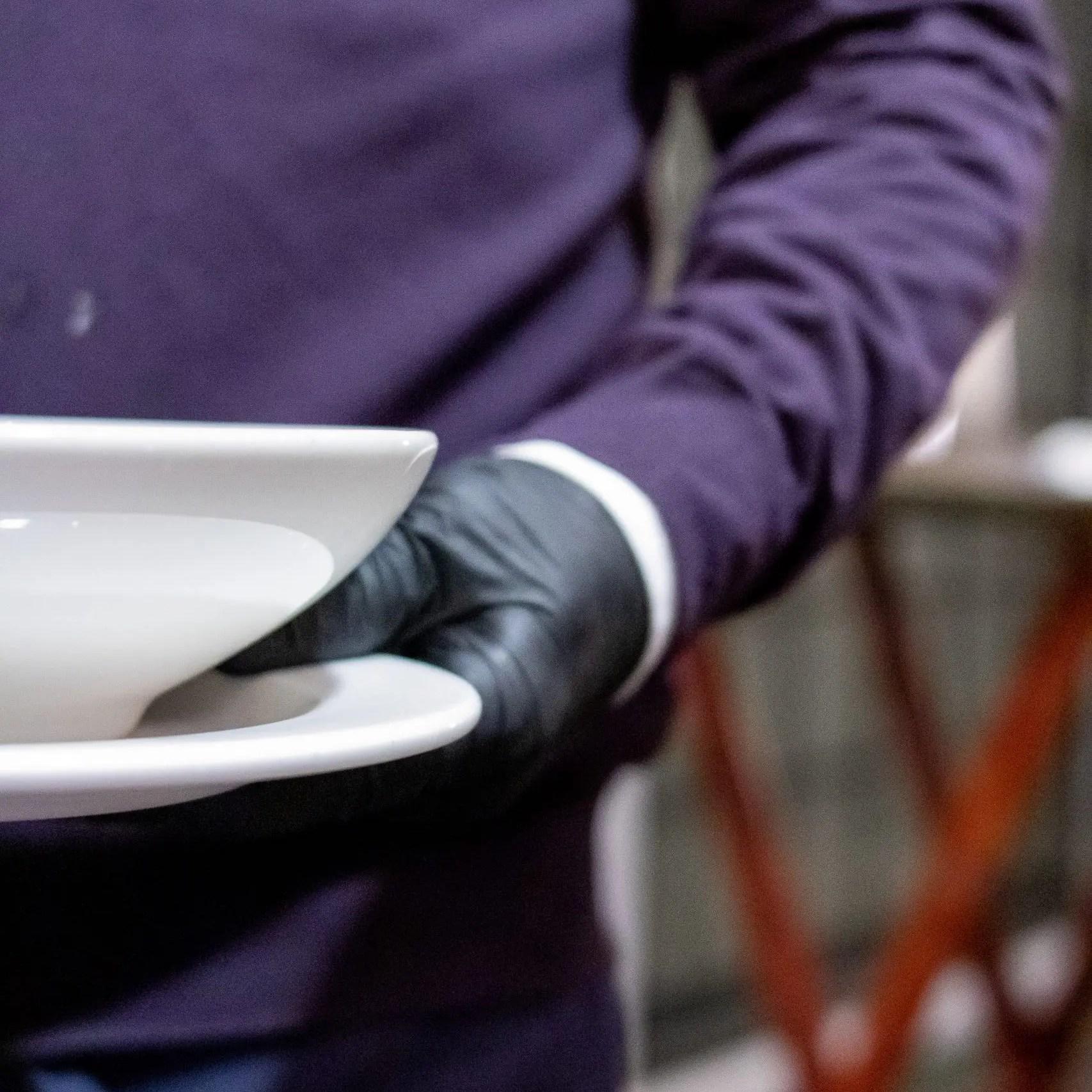 server wearing gloves to deliver food at Breeze Restaurant