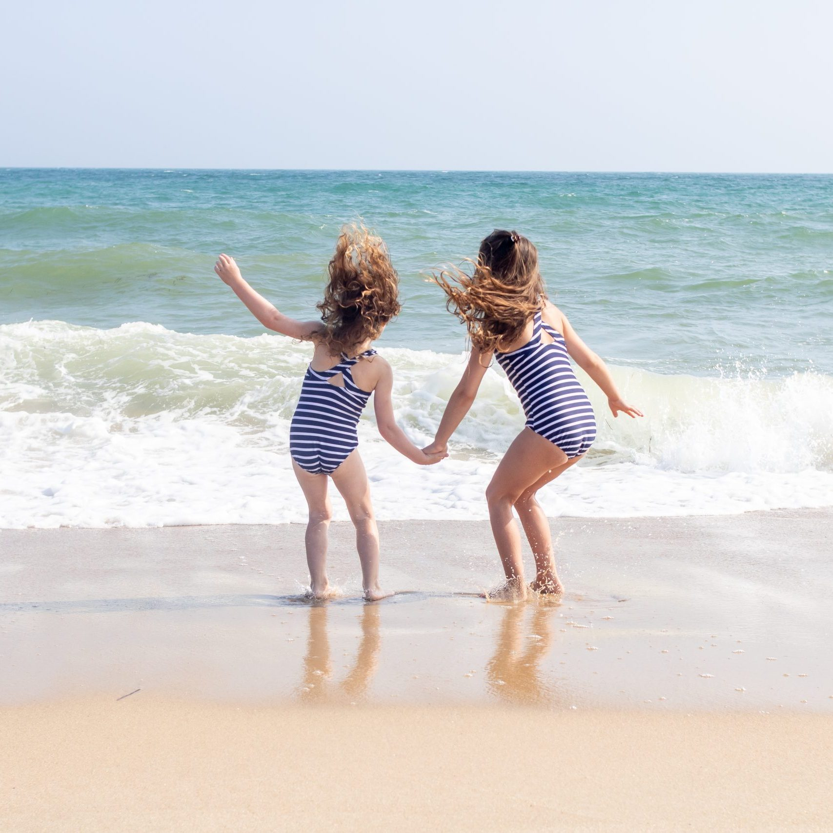sisters jumping in waves