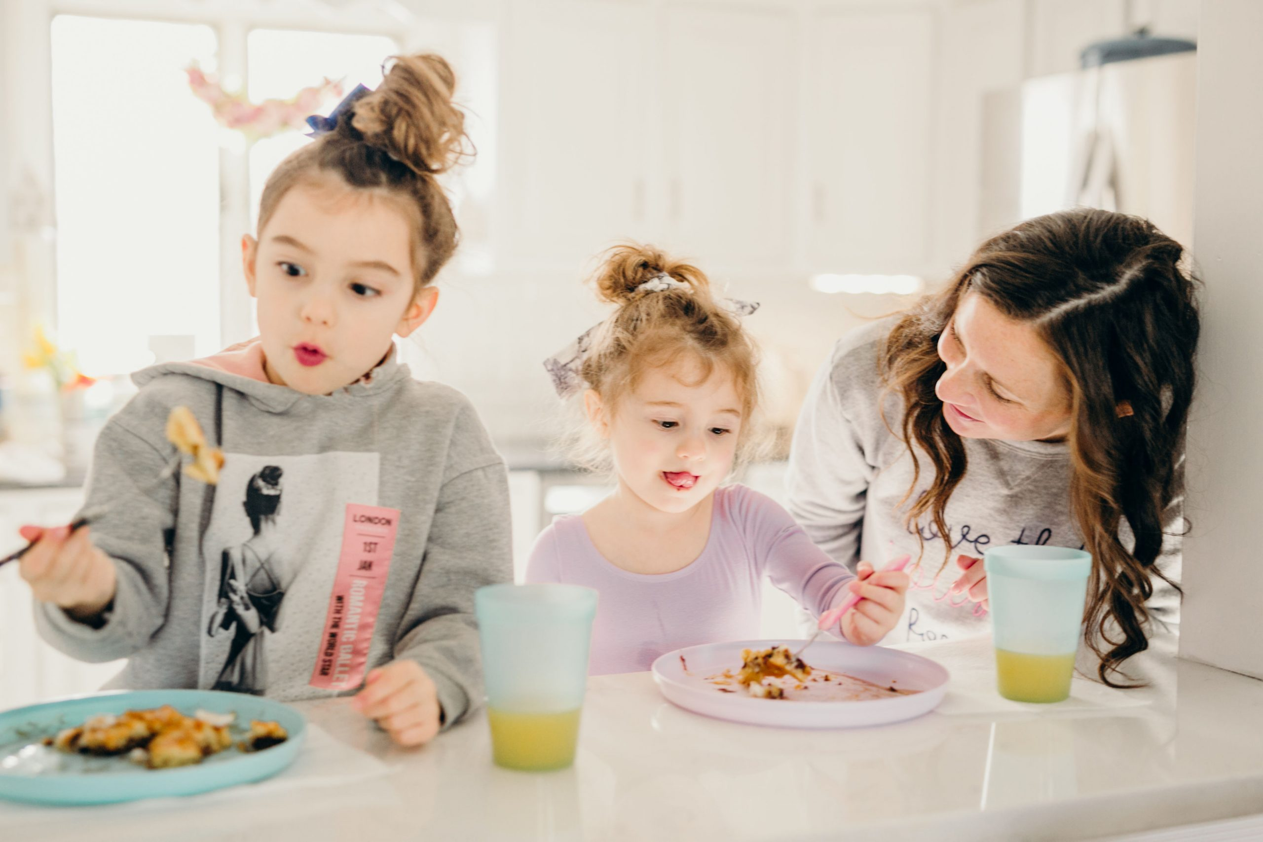 little girls sitting at breakfast bar eating pancakes with Mom