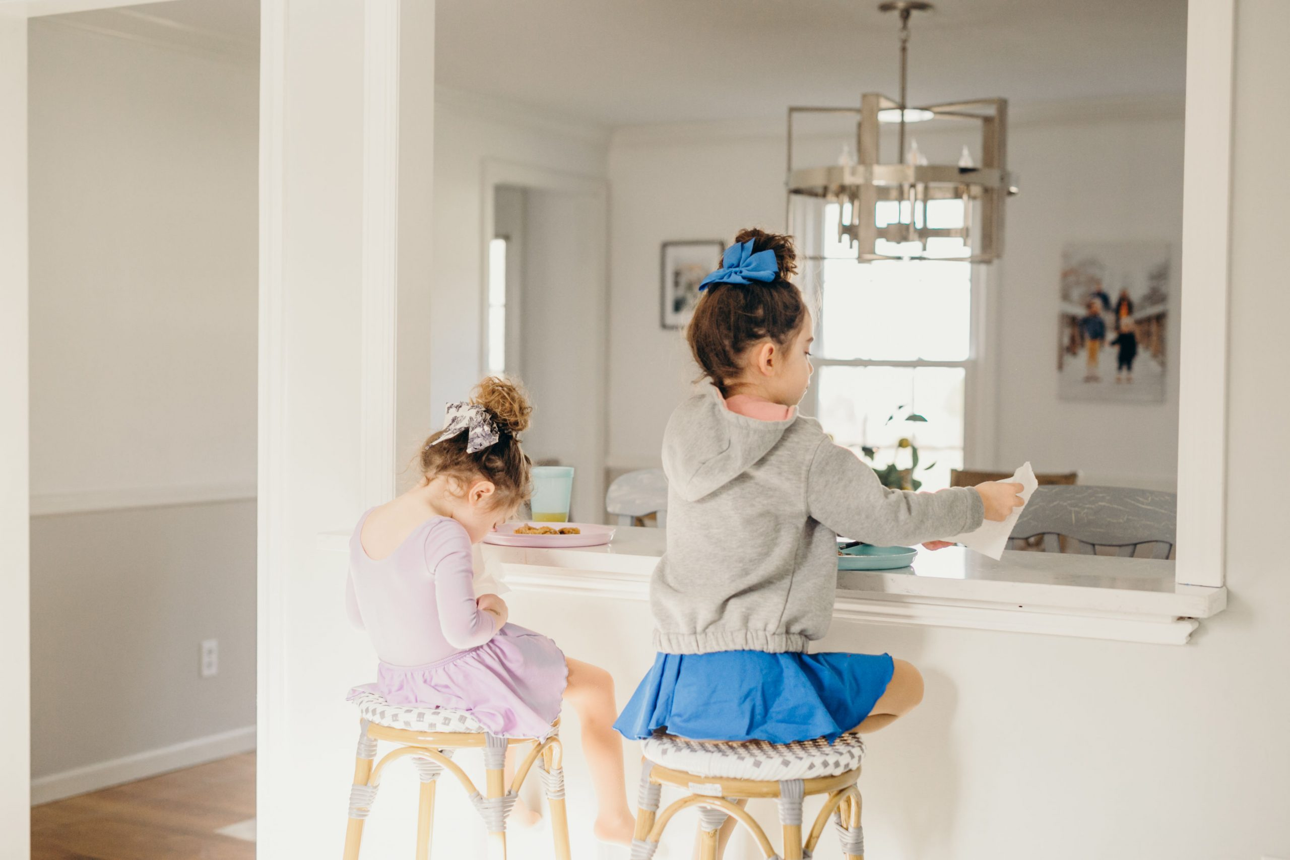 little girls sitting at breakfast bar eating pancakes