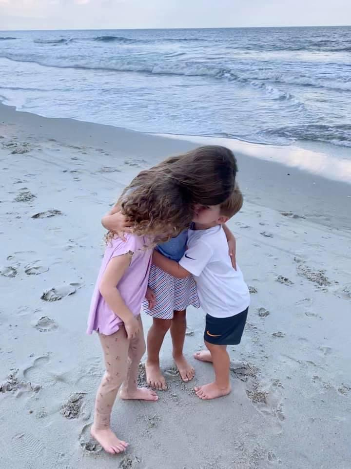 cousins hugging on beach in october