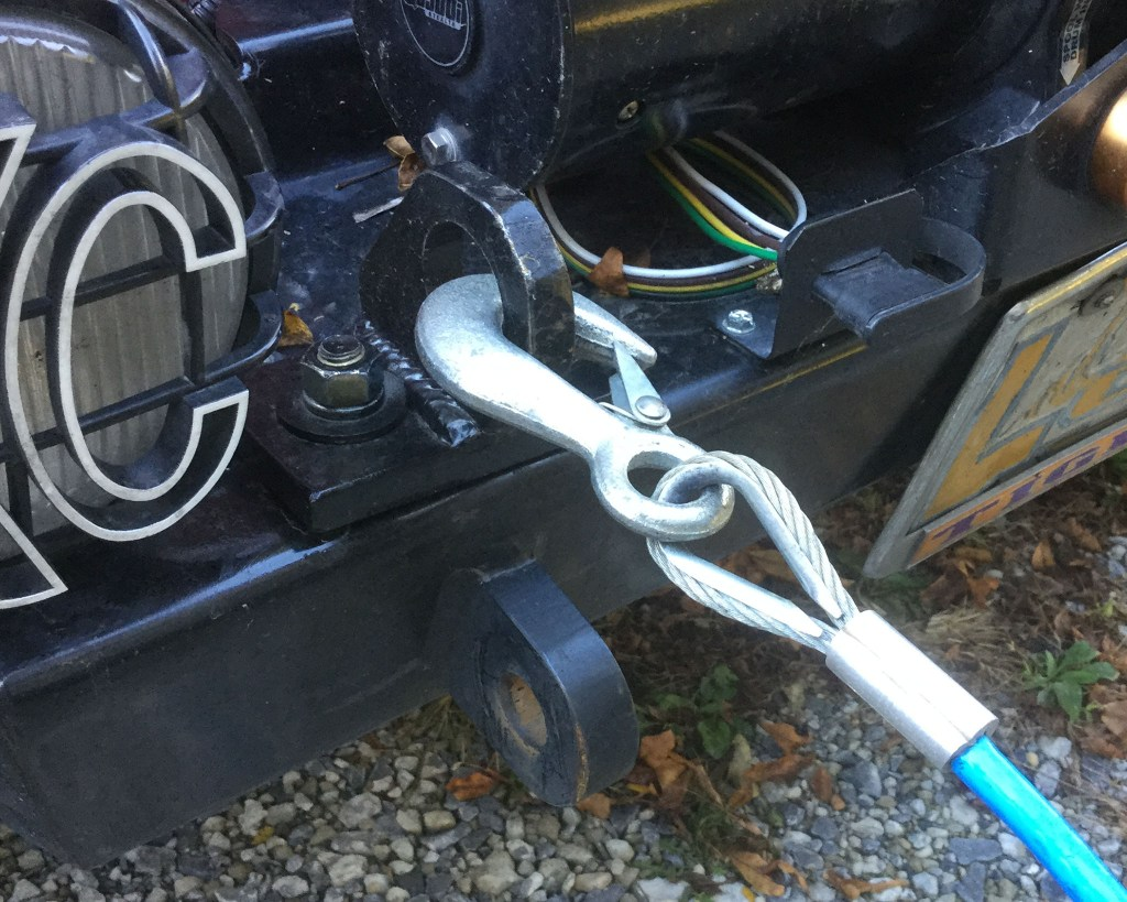 The original hardware, which failed, is removed and the safety cable pad-eyes are bolted in the same location. If the tow-rig fails, the cables will remain attached.