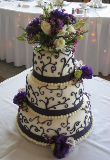 Three Tier Round Wedding Cake With Purple Flowers And