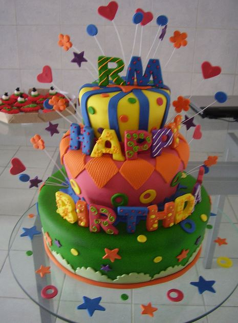 Three Tier Birthday Cake With Colorful Letters And Stars
