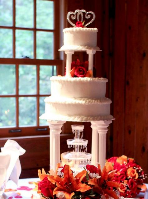 Multiple tier wedding cake with Roman columns and fontain with crystal topper and red rosesJPG