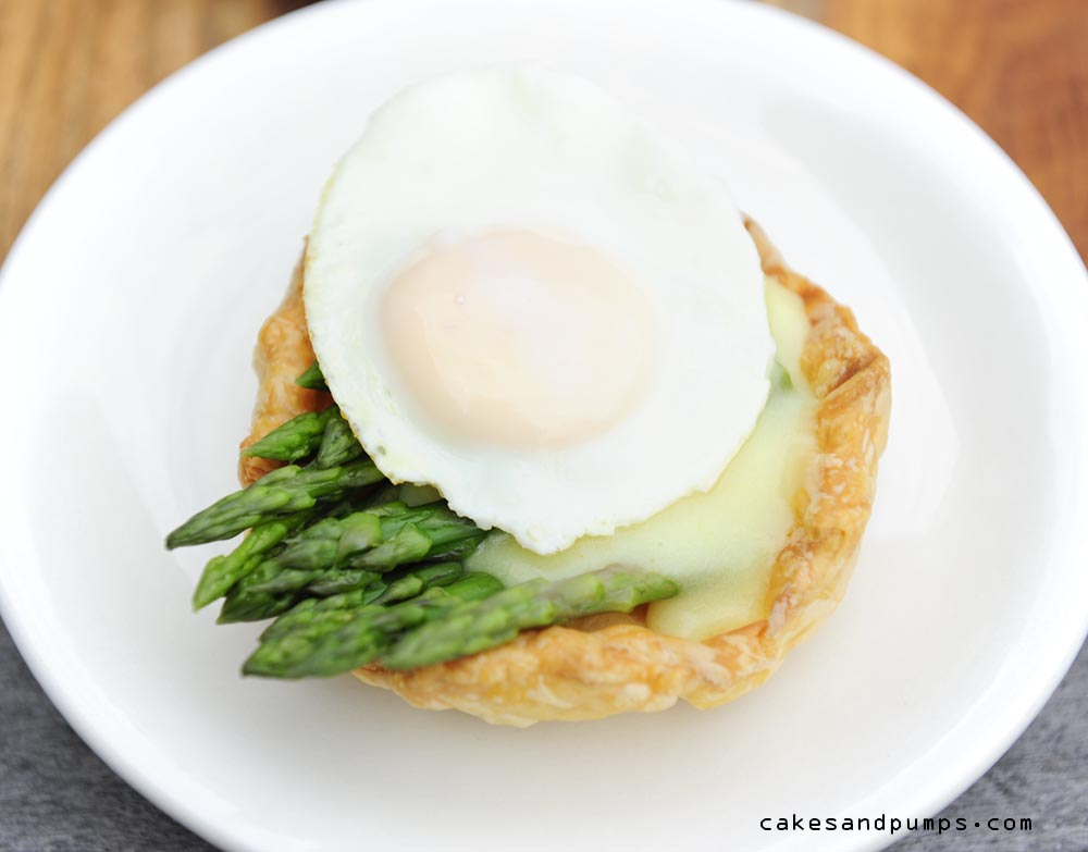 Little pie made of puff pastry with green asparagus, hollandaise sauce and a quail egg