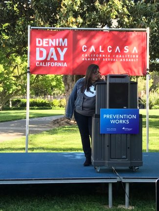 Red banner with white writing daying Denim Day and with CALCASA Logo in background. Latina women wearing denim jacket at podium with sign saying Prevention Works