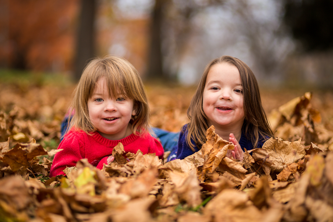 fall family photo of twin girls laying in the leaves