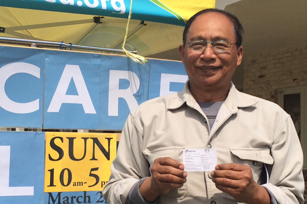 Marady Preap of Long Beach, proudly displays his new insurance card, though he said the process of getting covered was often confusing. Photo: Jessica Portner
