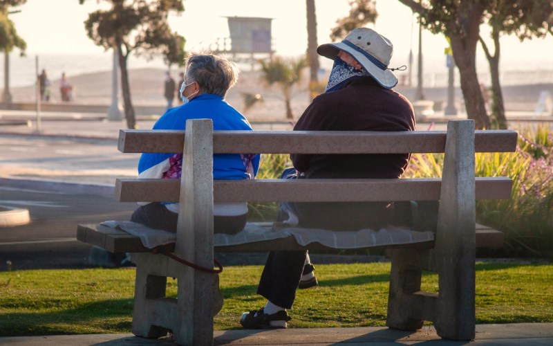 Two seniors wearing masks sit on a bench near Venice beach in mid-April.