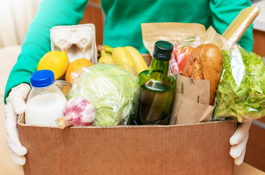 Woman in green shirt and protective gloves put delivered box with food products on wooden table in kitchen.