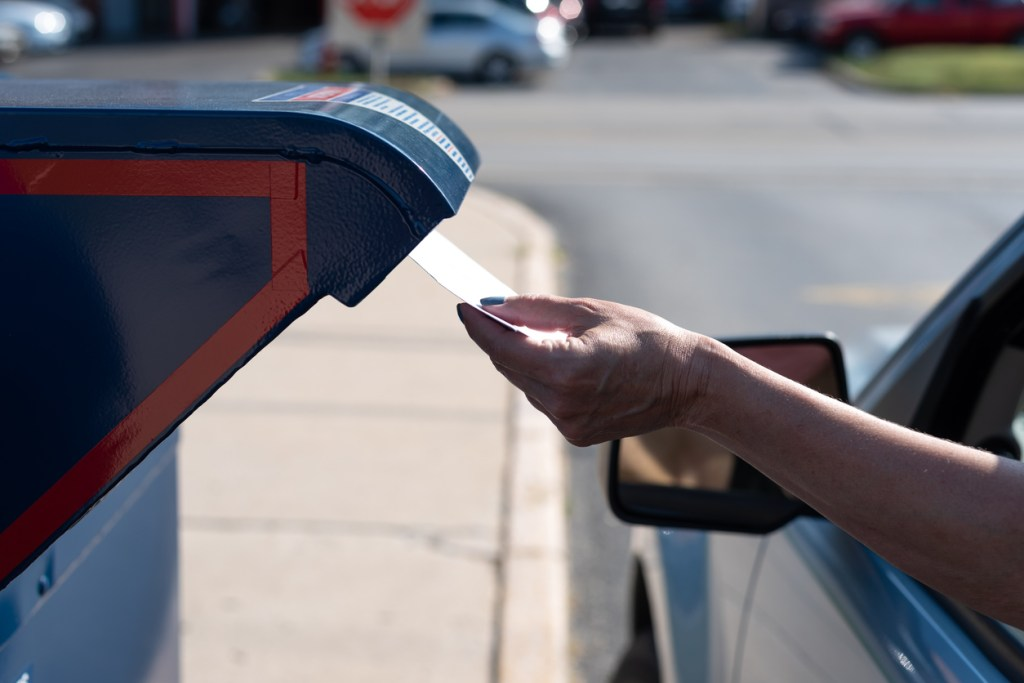 Safely mailing an application for ballot for 2020 election at a  drive-up mailbox at the US Post Office