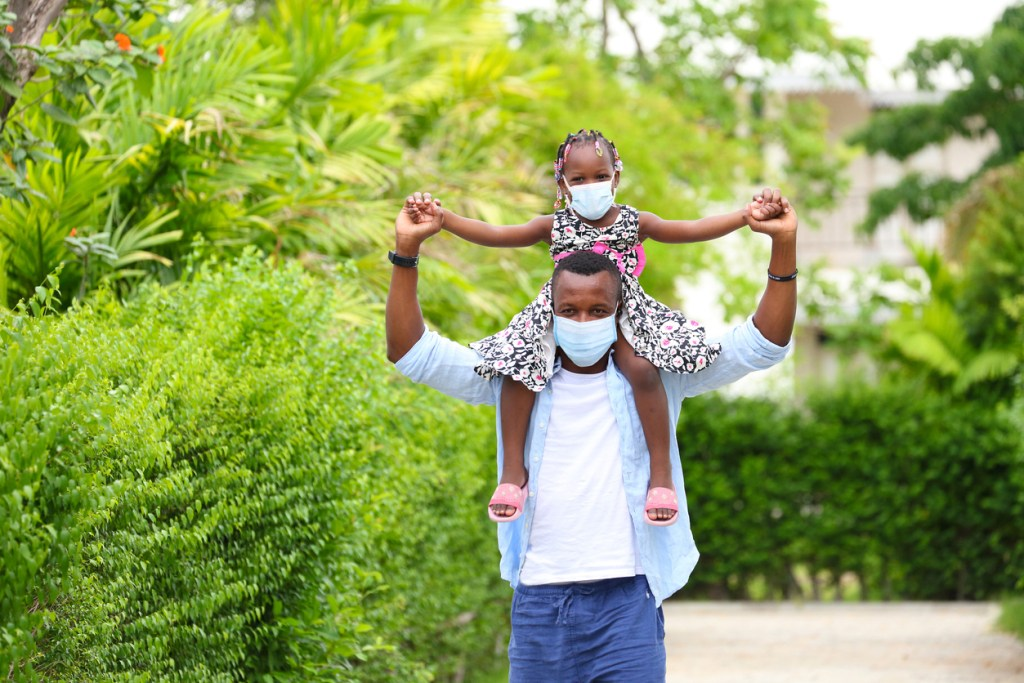 African American father gave piggyback ride to his little daughter and having a good time together walking around the neighborhood while wearing mask during social distancing and new normal