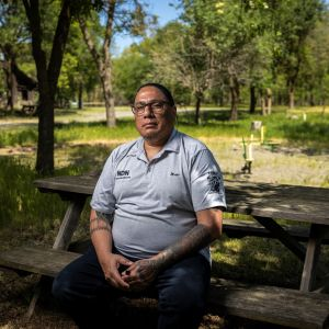 Mike Duncan, the founder of Native Dads Network, sits on a bench.