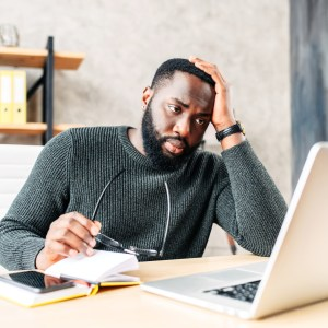 Frustrated sad black guy is watching at laptop screen