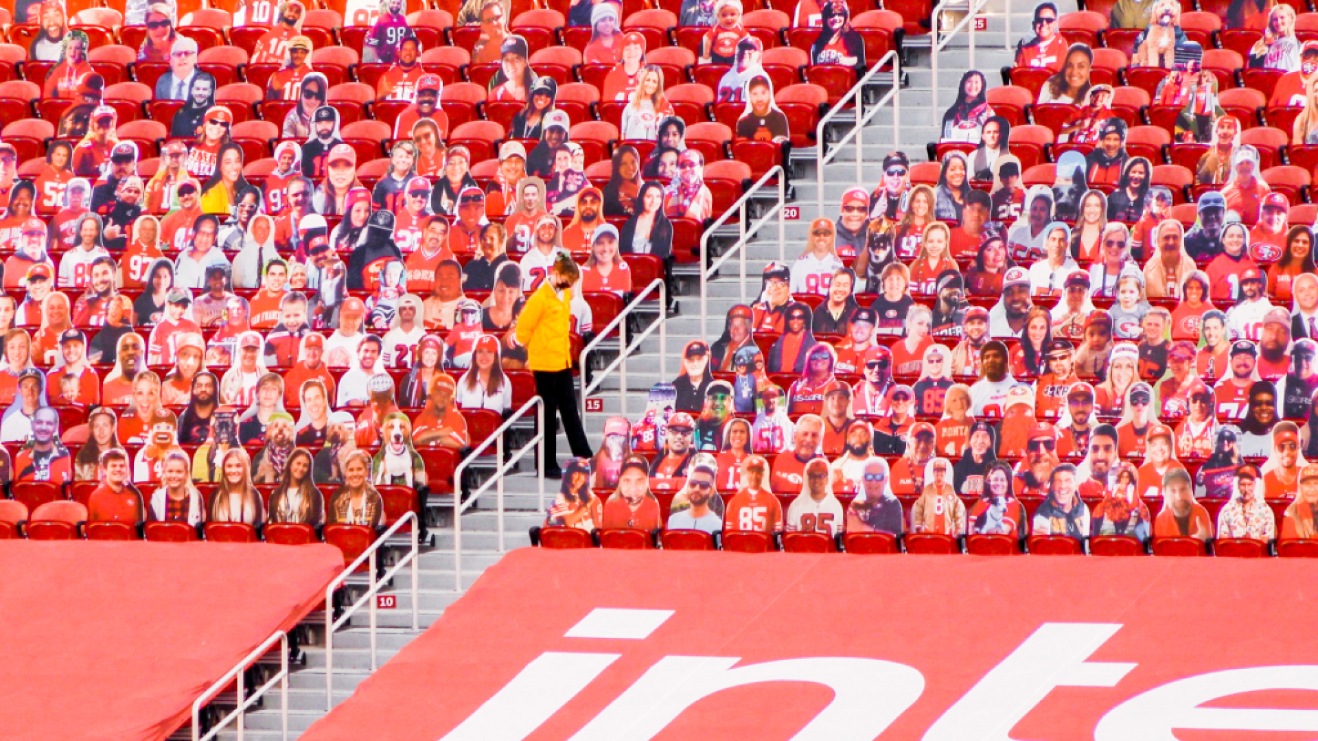 A lone stadium usher stands among rows of plastic fan cut-outs placed in empty seats