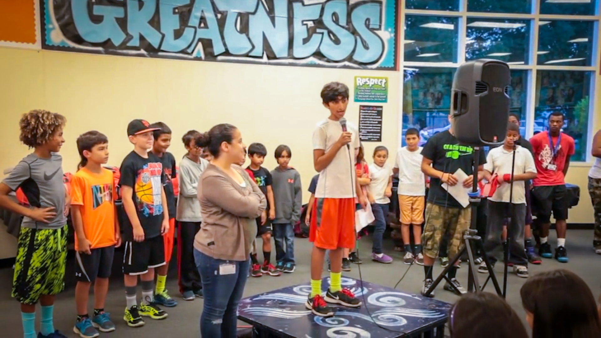 a 5th grade boy stands on a small stage in front of a gathering of other kids his age