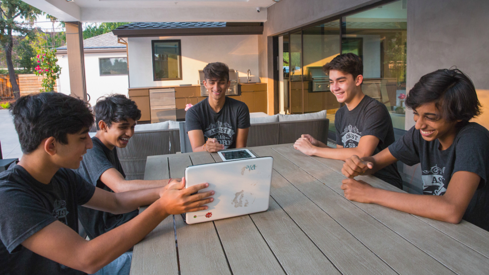 a group of middle school boys sits around a table outdoors with a laptop and a tablet