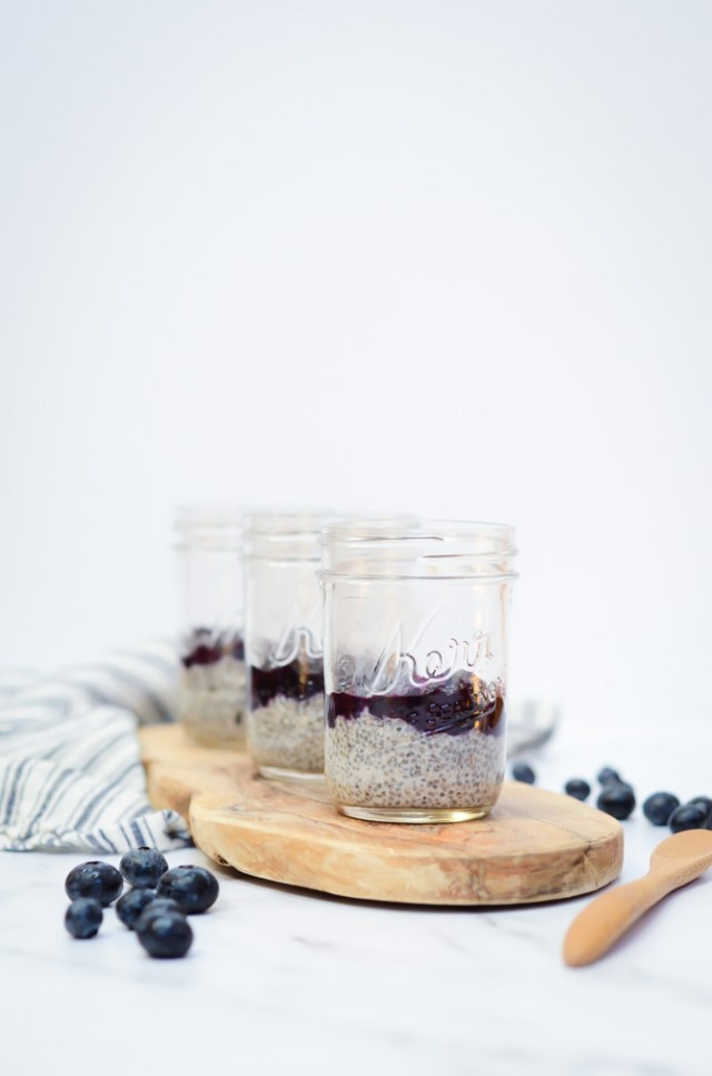 Three jars of Oat Milk Chia Pudding with Blueberry Orange Compote on a rustic wooden plank.