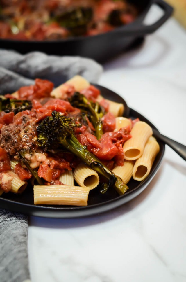 A plate of pasta topped with bison meatballs, broccolini and tomato sauce.
