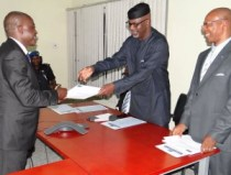 Gov Liyel Imoke, flanked by DG CRGIA, Clement Oshaka, hands C of O to a beneficiary