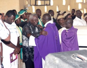 The priests share the sign of peace with the bereaved family