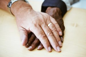 Mixed race older couple holding hands
