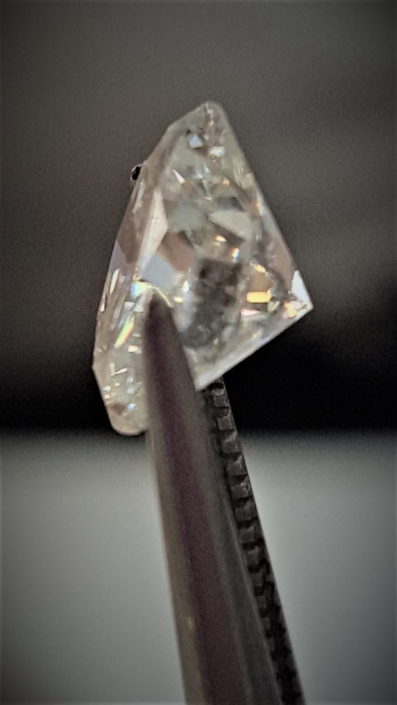 Profile pic of a diamond in tweezers.