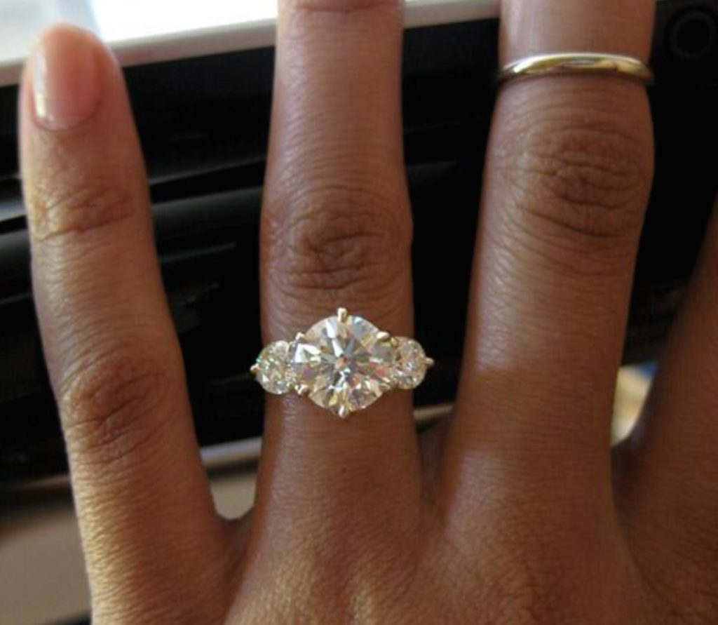 Three diamond engagement ring on African American hand