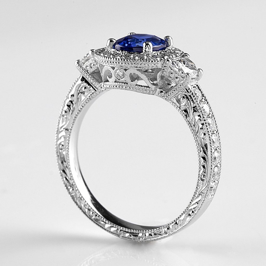 Hand engraving on top and sides of sapphire and diamond engagement ring