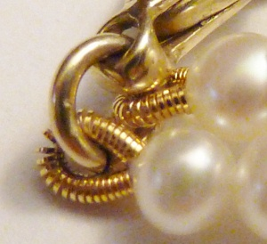 French wire finish by clasp of pearl necklace.