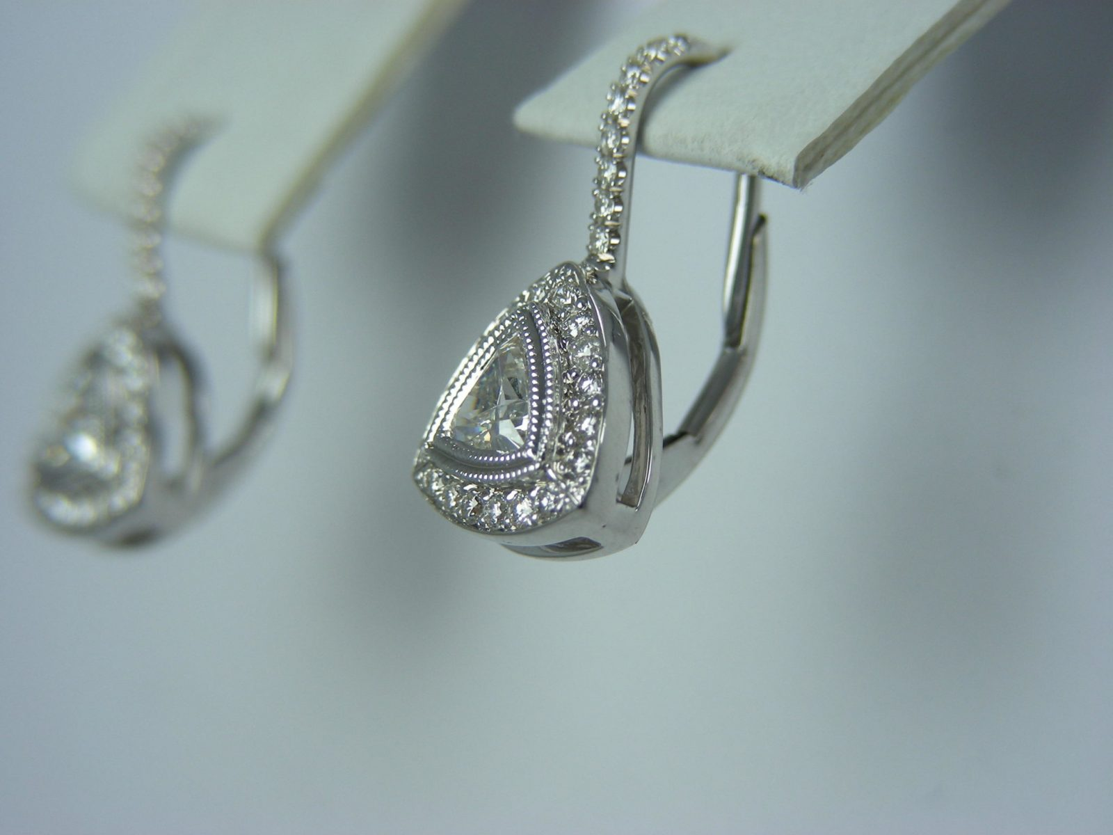 lever backed diamond earrings with trillian diamond and halo of tiny diamonds.