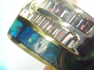 Inlaid opal and diamond ring showing a chip in inlaid opal
