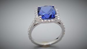 cushion cut blue sapphire with diamond halo engagement ring.