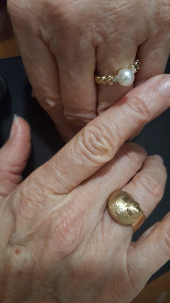 two rings, one pearl on scalloped yellow gold band and large shell in yellow gold ring
