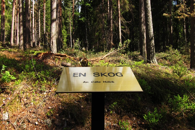 "7 epic sculptures - a sign in front of the art work ""a forest - by: Calle Holck"" and behind the sign is a real forest."