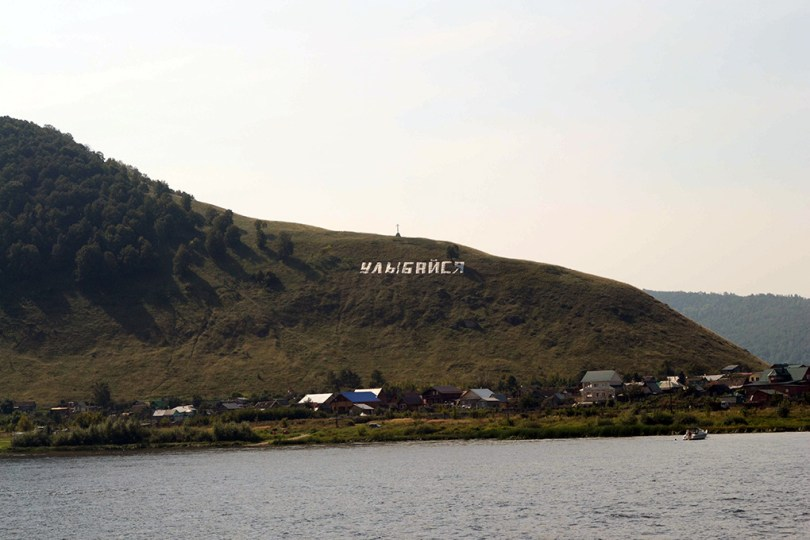 A picture taken from a lake, far away from the mountain that has large white letters on it, that says Smile in russia