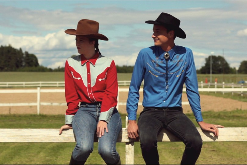 Still image from the video Twenty Happy Endings. Two people are sitting at a white painted fence. They both look like cowboys.