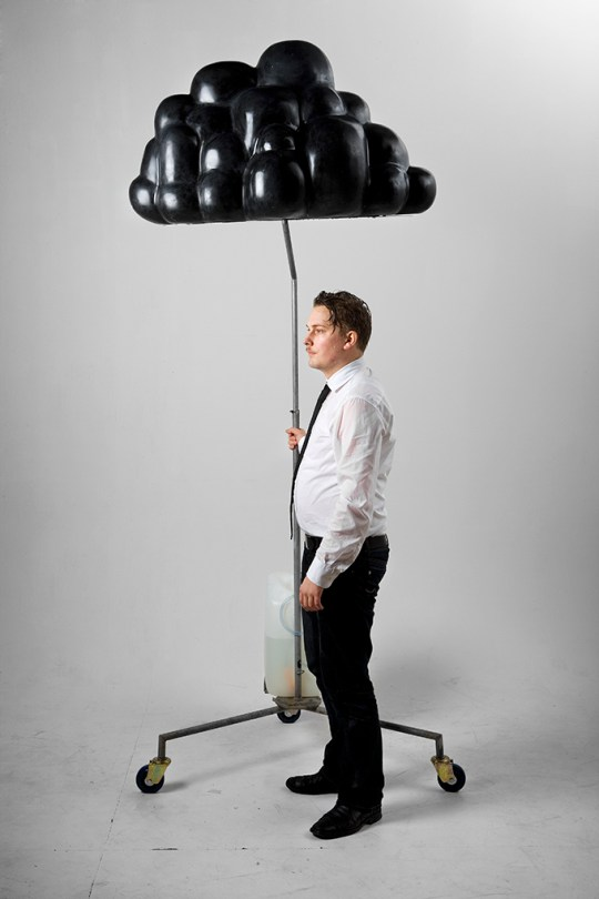Artist Calle Holck standing under the black cloud that's on a metal stand.