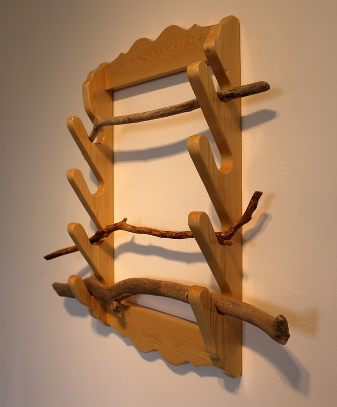 A wodden rack of some sort where three sticks in different shapes carefully have been hung