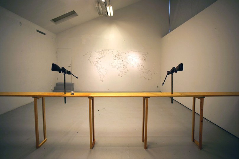 Shoot World Two rifles on a wooden bench, aimed at a world map