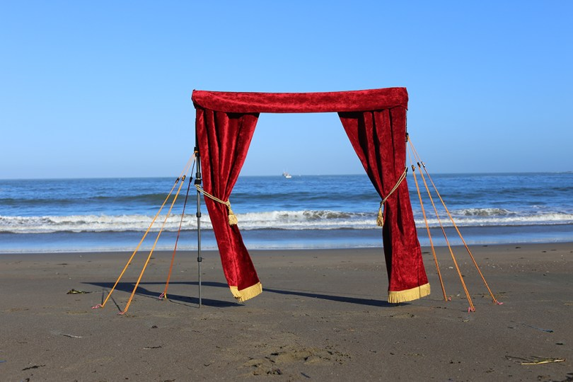 Travel Curtain. A drop curtain (like one from a theater stage) detached from the stage. Here it is standing in front of the pacific.