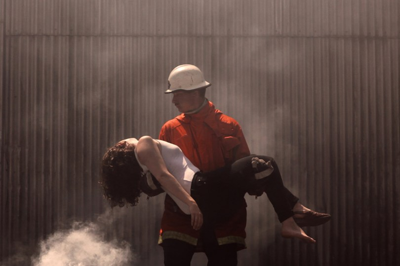 Still image from the video Twenty Happy Endings. A firefighter is walking out of a burning building with a passed out woman in his arms.