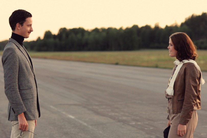 Still image from the video Twenty Happy Endings. Two people are looking at each other, standing at a runway. One of them seems to be dressed like an old pilot.