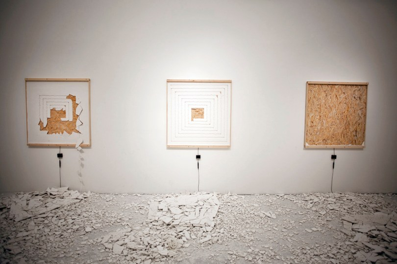 Plaster Blaster. Three white boxes with rope underneath them, where people have pulled the ropes and changes the boxes. On the floor there are a lot of white crushed things.