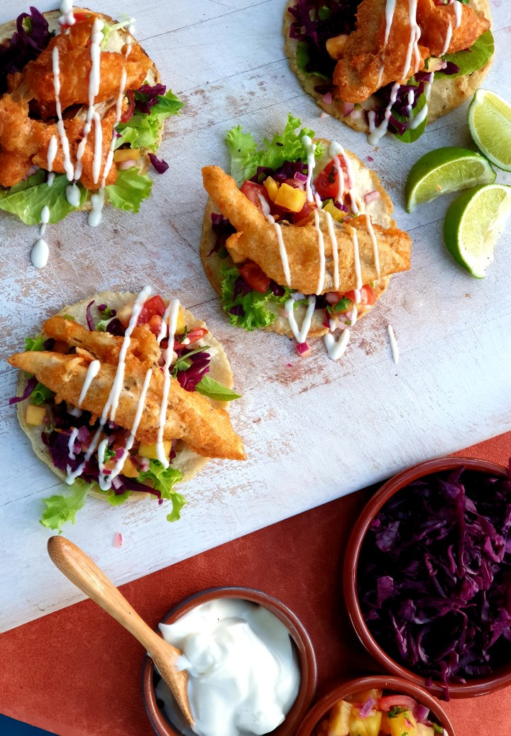 a cutting board with crispy baja fish(less) tacos , pineapple salsa and a drizzle of lime mayo with sides dishes of mayo and curtido