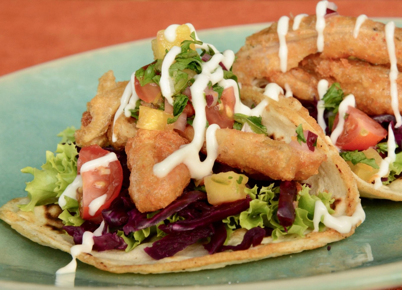 Plate of crispy battered Baja Fish(less) Tacos drizzled with lime mayo